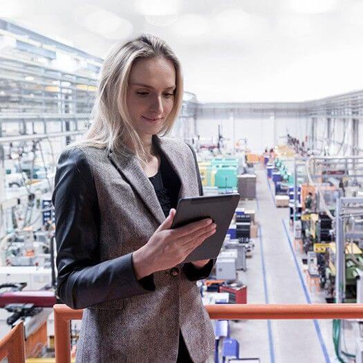 Business woman using tablet on manufacturing floor
