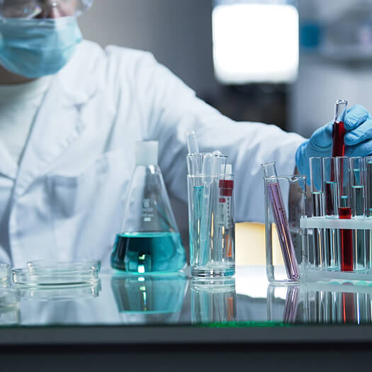 Clinical lab worker in lab coat and mask