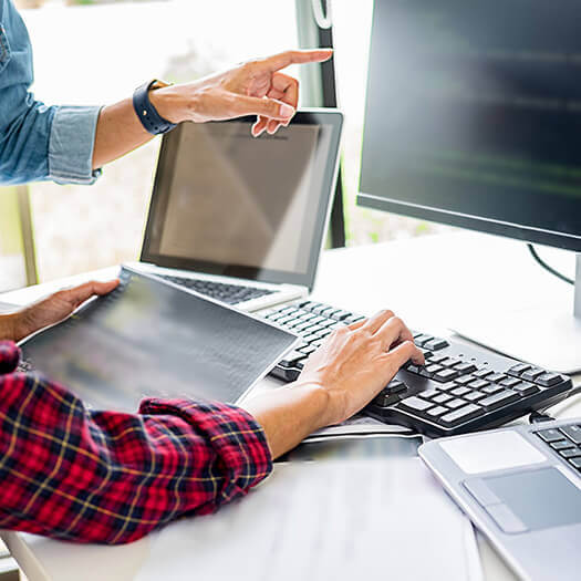 Office workers using a computer and laptop