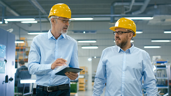 Two factory workers talking and using a tablet