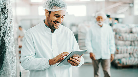 Manufacturing worker in lab coat using a tablet