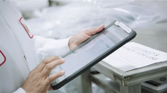 Person in a lab coat using a tablet in a factory